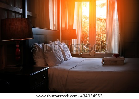 Bed maid-up with clean white pillows and bed sheets in beauty room. Close-up. Lens flair in sunlight. Sunrise garden view on the background - stock photo