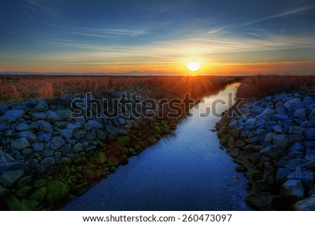 Bed of rocks by the riverside at sunset - stock photo