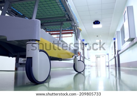 Bed on wheels waiting in the illuminated hospital corridor - stock photo