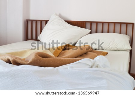Bed room,Interior shot of motel room with messy unmade bed. - stock photo