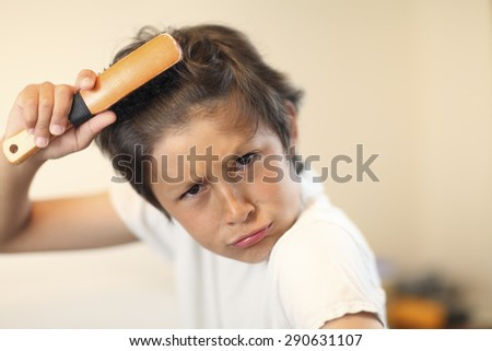 Bed time - boy brushes his hair - very shallow depth of field - stock photo