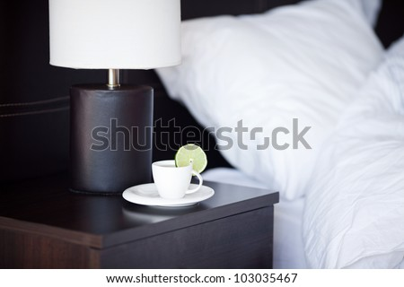 bed with a pillow, a cup of tea on the bedside table and lamp - stock photo