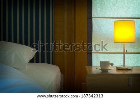 bed with a pillow, a cup of tea on the bedside table and lamp.   - stock photo