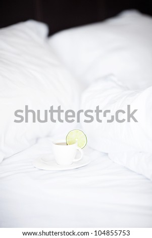 bed with a pillow and a cup of tea - stock photo