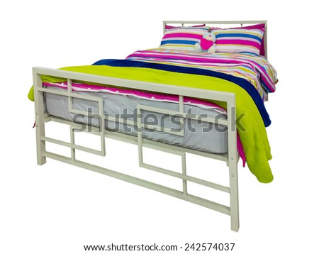 Bed with colorful duvet and cushions isolated on white. - stock photo