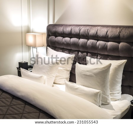 Bed with pillows and headboard and a night table lamp to the left. - stock photo