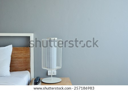 Bed with white linen beside night table with lamp. Minimalism interior. - stock photo