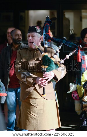 BEDFORD, ENGLAND  NOVEMBER 2014: Remembrance Day Parade - Scottish Military Marching Band bagpiper playing, shown on 9 November 2014 in Bedford - stock photo