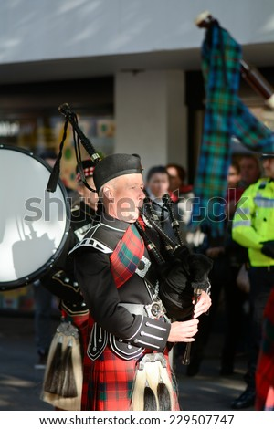 BEDFORD, ENGLAND  NOVEMBER 2014: Remembrance Day Parade - Scottish Military Marching Band member playing bagpipes, shown on 9 November 2014 in Bedford - stock photo