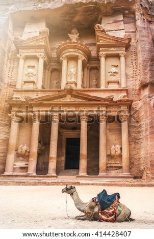 Bedouin camel rests near the treasury Al Khazneh carved into the rock at Petra, Jordan. The city of Petra was lost for over 1000 years. Now one of the Seven Wonders of the Word - stock photo