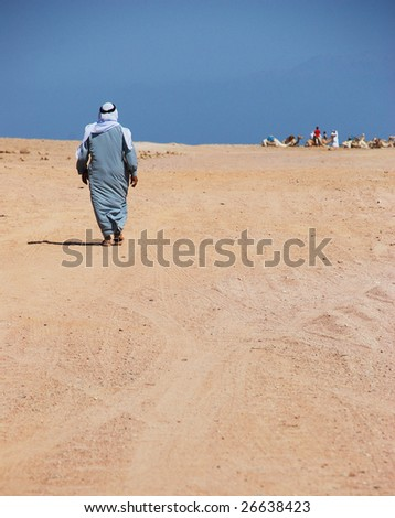 Bedouin man walking though the desert. Egypt. For other similar images from the series, please, check my portfolio. - stock photo