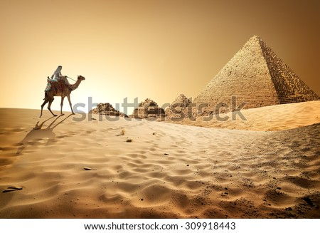 Bedouin on camel near pyramids in desert - stock photo