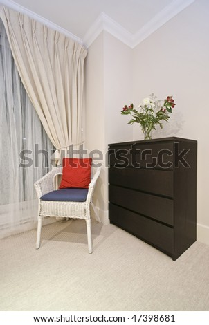 Bedroom detail in night with rattan armchair and wooden chest of drawers - stock photo