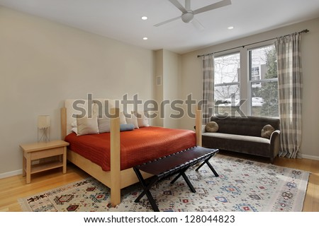 Bedroom in luxury home with tan walls - stock photo