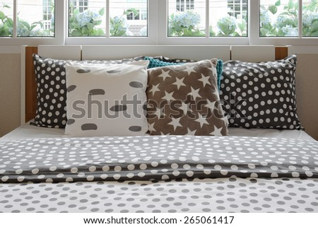 bedroom interior design with polka dot pillows on bed and decorative bedside table lamp. - stock photo