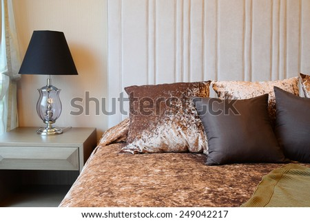 bedroom interior design with tweed brown pillows on bed and decorative table lamp. - stock photo
