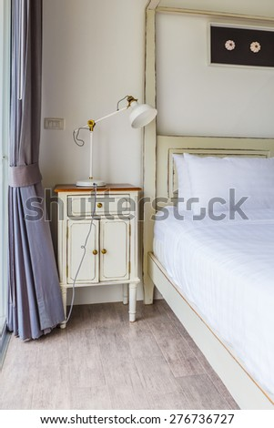 bedroom interior design with White pillows on white bed and decorative table lamp - stock photo