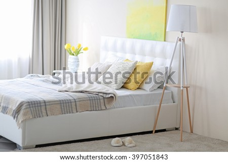 Bedroom interior in light tones with white furniture and pictures on the wall - stock photo