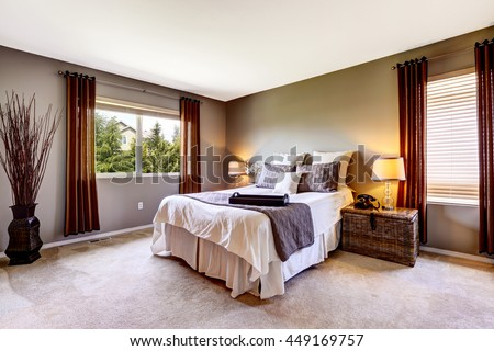 Bedroom interior with carpet floor and big bed. American northwest house - stock photo