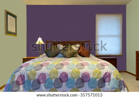 bedroom interior with purple and green walls lamp colorful pillows and comforter decorating queen size bed  - stock photo