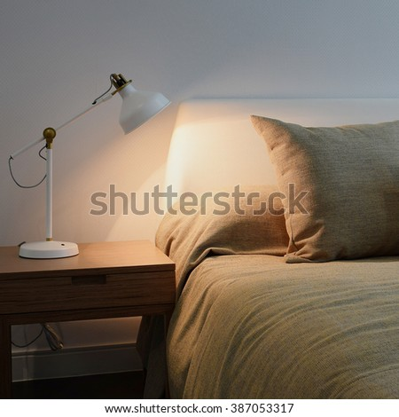 bedroom interior with reading lamp on bedside table - stock photo