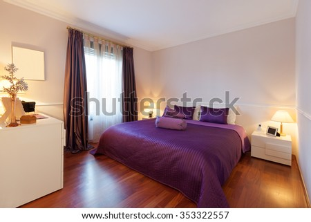 bedroom of a modern apartment, double bed with purple bedspread - stock photo