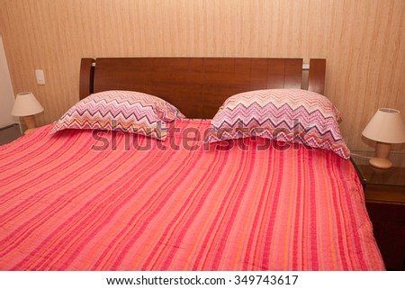 Bedroom with bed made red cover and pillows - stock photo