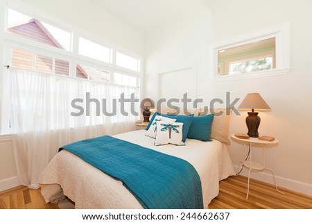 Bedroom with blue bed sheets with night stands and natural fibers rug - stock photo
