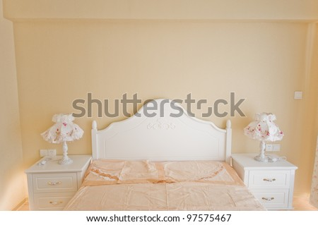 bedroom with comfy white headboard and beautiful lamp. - stock photo