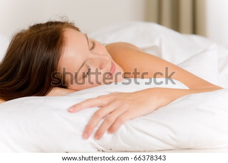 Bedroom - young woman sleeping and dreaming in white bed - stock photo