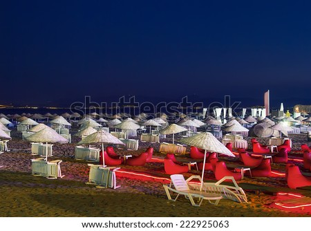 Beds and straw umbrellas on Sarimsakli Beach, Turkey At Night - stock photo