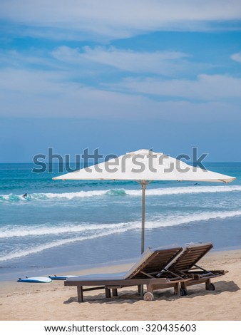 beds and umbrella on a tropical beach - stock photo