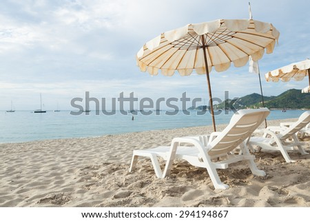 Beds and umbrellas on the beach. The seaside beach tourist attractions. - stock photo