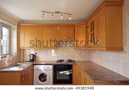 Beech kitchen units in UK home - stock photo