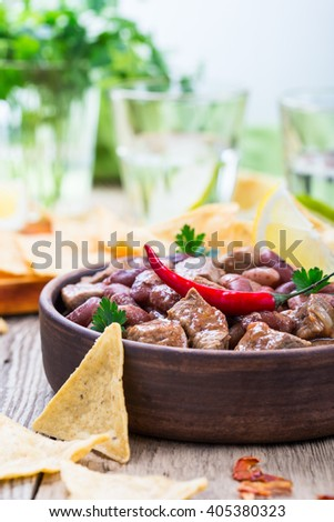 Beef and black bean chili served with corn tortilla chips on rustic wooden table, mexican food - stock photo