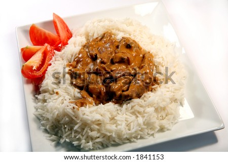 Beef and mushroom stroganoff on a bed of rice, garnished with tomato - stock photo