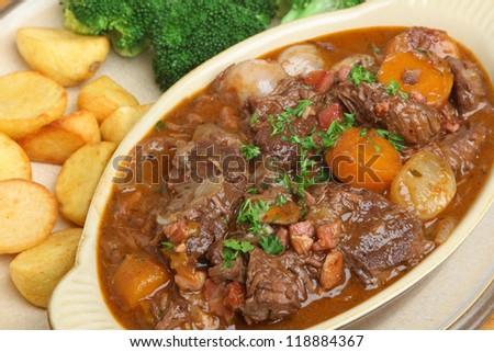 Beef bourguignon stew with roast potatoes and broccoli - stock photo