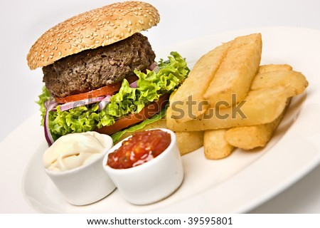 Beef Burger in bun with chips and relish - stock photo