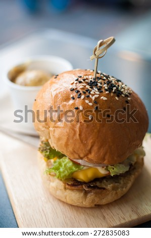 Beef burger on wooden plate in restaurant - stock photo