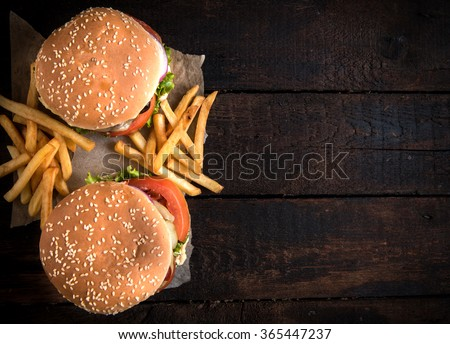 Beef burgers and french fries on wooden background with blank space  - stock photo
