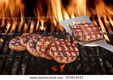 Beef Burgers And Spatula On The Hot Flaming BBQ Charcoal Grill, Close-up, Top View - stock photo