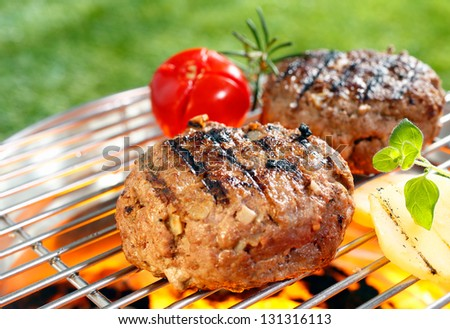 Beef burgers cooking on grilling pan outdoors - stock photo