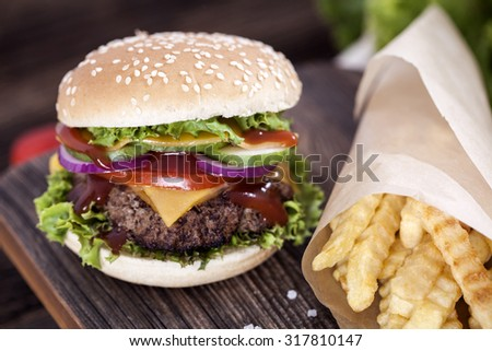 Beef burgers on a wooden board with chips and aromatic spices. Studio Shot - stock photo