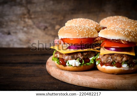 Beef burgers on the wooden background with blank space on left side - stock photo