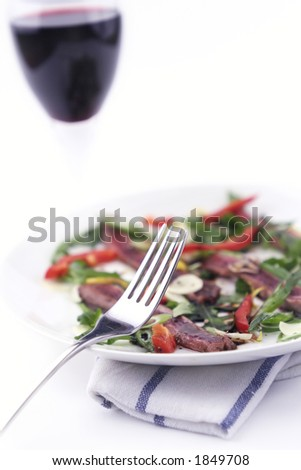 Beef carpaccio on a white plate with glass of red wine. Shot against a washout white background and shallow depth of field. Focus on fork and salad. - stock photo