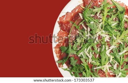 Beef carpaccio on red background - stock photo