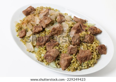 Beef, cooked with onion and spices and served on a bed of frikeh, fire-roasted green wheat, an Arab recipe. - stock photo