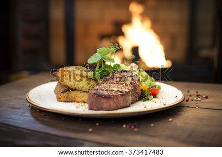 Beef dinner - Delicious grilled stake and potatoes served on a wooden table, fireplace on background - stock photo