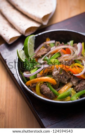 Beef fajita in the pan with tortilla bread. - stock photo