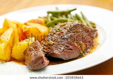beef fillet steak with potatoes and beans - stock photo